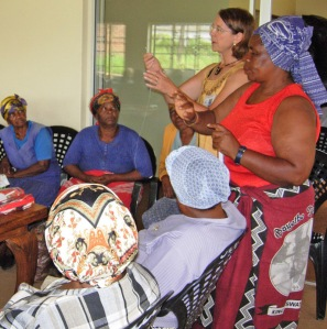 Attentive South African grandmothers learn sewing skills from Beverley Barling in an effort to improve the hardships in their lives