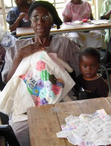 Gogo sews her work to a blanke as her grandson watches.
