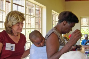 Susan Fenner of Grannies à Gogo looks at a sleeping child on the back ofhis grandmother who is learning sewing skills taught by Beverley Barling.