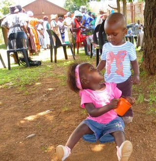 A couple of grandchildren play while their gogos collect food in the background