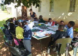 With no room indoors, Benedicte oversees 15 little ones with their homework and supplementary exercises, on a ping-pong table under a tree.