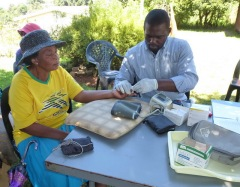 Doris Dhlamini has her blood sugar tested by Jonathan, who is pinch hitting for retired nurse Cornelia.