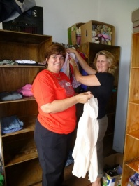 Joy Comley (right) and friend Ena Chandler begin to set up the Clothes Bank.