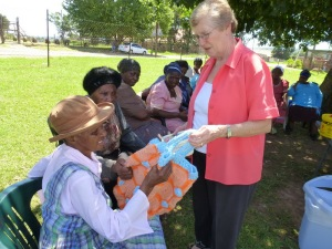 Volunteer Joy Burton (standing) helps the gogos with their various handicrafts. Here she discusses 88 year-old Inah Mashego's crocheted bag.