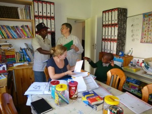 Samuel Fenyane (from the Teachers Union) and Vicky Bryant look at materials. Benedicte assists a young learner.