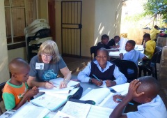 Susan helps a table of grade 4s with maths homework